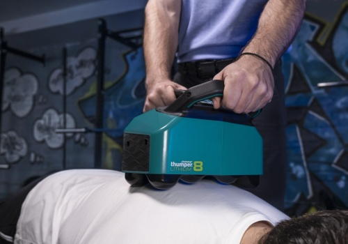 Lithium8 is the first battery-powered Thumper and the only percussive massager of its kind. Model being massaged on his back.